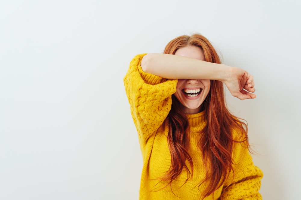 Shutterstock_1188599524 woman covering her eyes with her arm while waiting for a surprise
